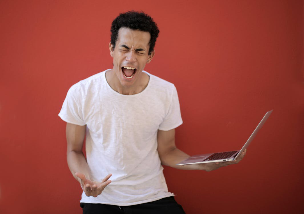 young male with laptop screaming